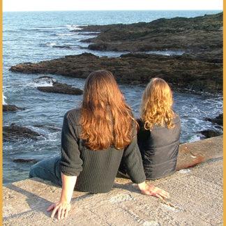 Heather and Ben sitting on an ocean pier